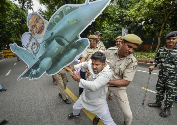 Police detain a youth Congress member carrying a model of a plane during a protest over Rafale deal issue outside the AICC office in New Delhi, on Saturday. PTI