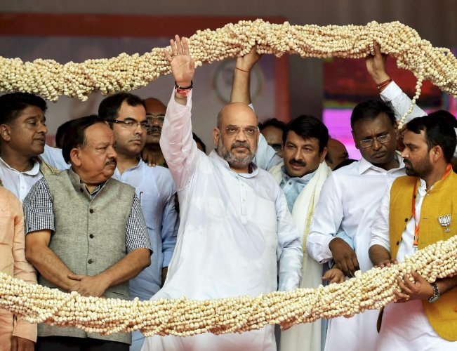 BJP President Amit Shah with other senior leaders being garlanded during the Purvanchal Mahakumbh, at Ramleela Maidan in New Delhi on Sunday. PTI