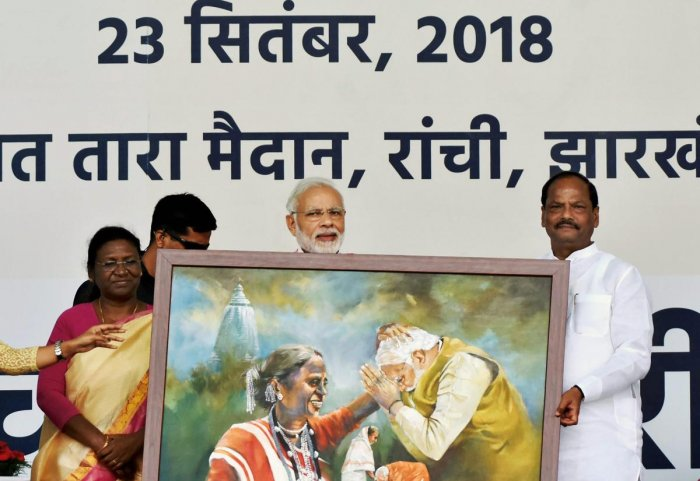 Prime Minister Narendra Modi being presented with a tribal art by Jharkhand Chief Minister Raghubar Das during the inauguration of 'Pradhan Mantri Jan Aarogya Yojna Ayushman Bharat Scheme', in Ranchi, Sunday, Sept 23, 2018. (PTI Photo)