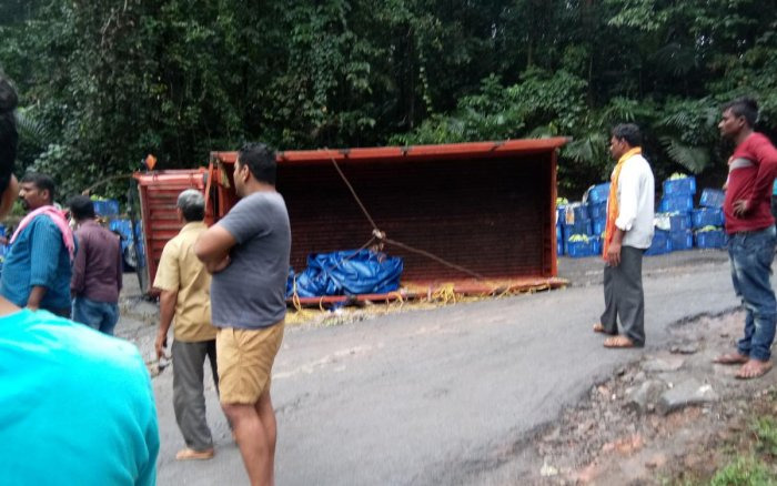 A lorry overturns on a Charmadi Ghat road on Wednesday morning.
