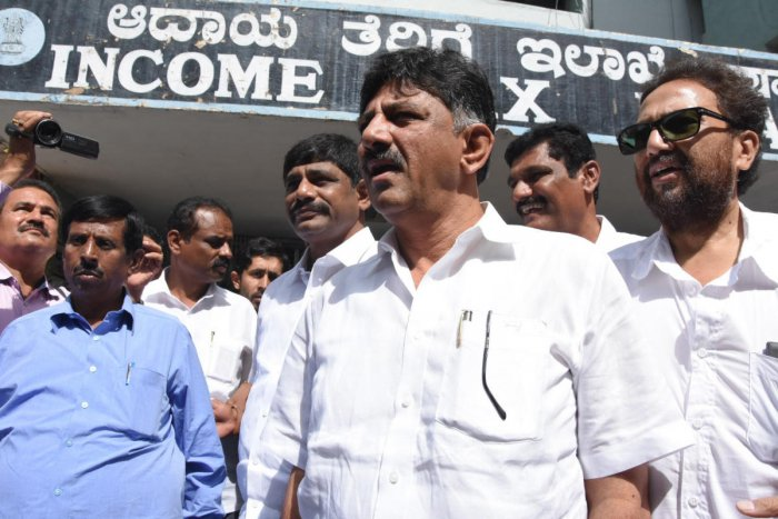 Minister D K Shivakumar and his brother and parliamentarian D K Suresh (second from left) walk out of the Income Tax office after questioning by officials, in Bengaluru. (DH File Pic)