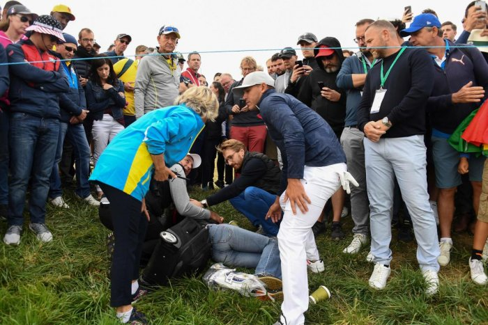 OPENING BLUES Brooks Koepka (right) checks on a woman after his wayward tee shot struck her on the face. AFP