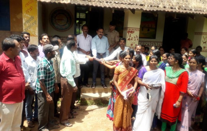 SDMC members and parents stage a protest outside BEO's office in Koppa against the suspension of Niluvagilu Government Primary School headmaster A E Ashok.