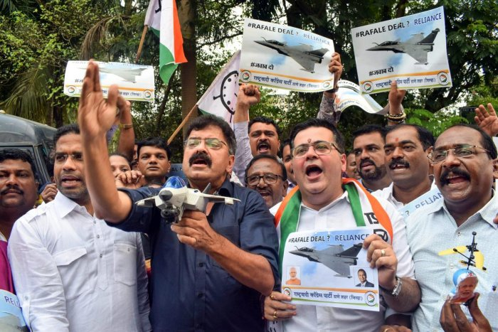 NCP workers raise slogans and placards during a protest against the alleged scam in Rafale deal, in Thane, on Friday. PTI
