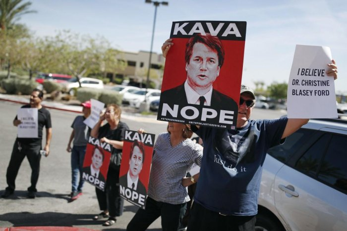 People hold signs during a protest against Supreme Court nominee Brett Kavanaugh outside the offices of Sen. Dean Heller, R-Nev., in Las Vegas. (AP/PTI Photo)