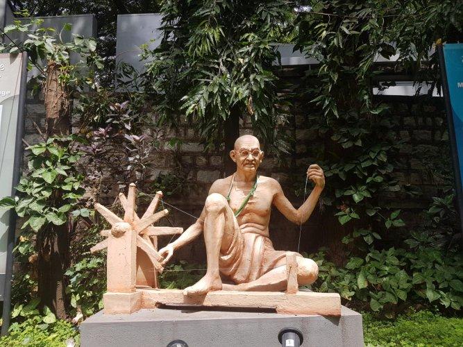 A sculpture of Gandhi and his charkha in Gandhi Bhavan.