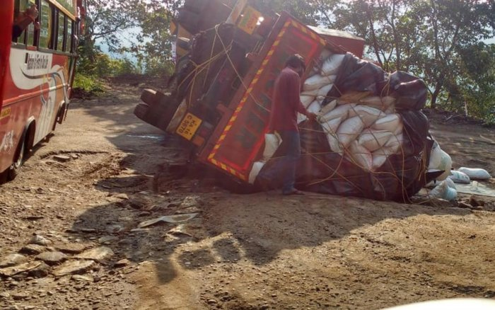 The lorry which toppled on Charmadi Ghat stretch.