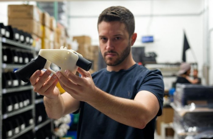 """Cody Wilson, owner of Defense Distributed company, holds a 3-D printed gun, called the """"Liberator"""", in his factory in Austin, Texas on August 1, 2018. AFP"""