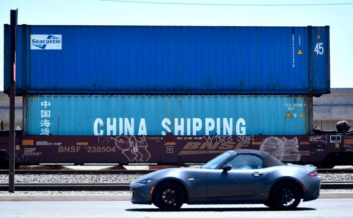 A motorist drives past shipping containers from China Shipping in at the Port of Long Beach in California on on July 12, 2018. AFP