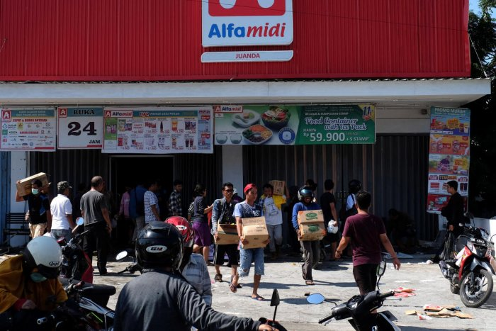 People make off with goods from a shop in earthquake and tsunami-devastated Palu, Central Sulawesi, Indonesia September 30, 2018. (REUTERS/Stringer)