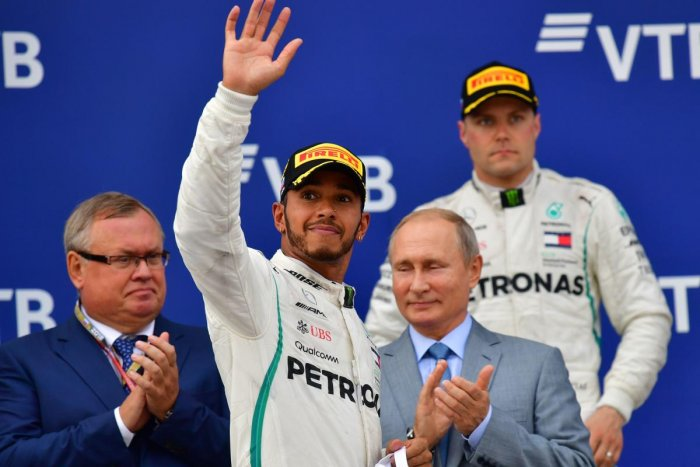 Lewis Hamilton celebrates as team-mate Bottas and Russian President Vladimir Putin look on.
