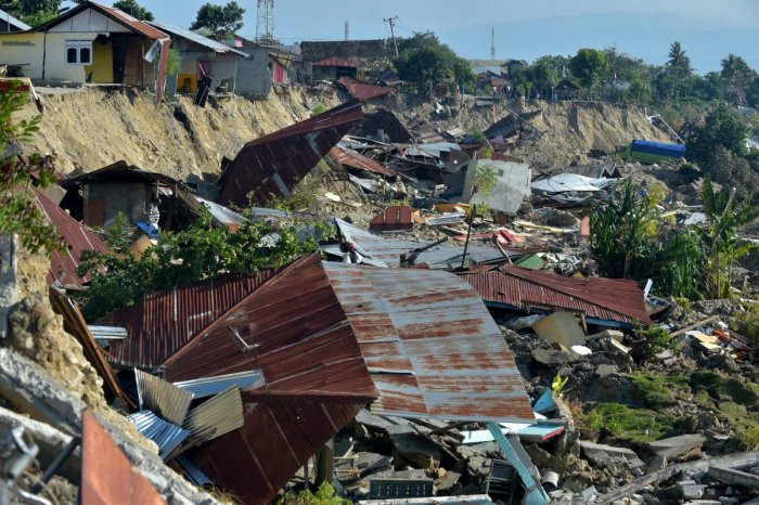 Damaged houses are seen in Palu, Indonesia's Central Sulawesi on October 1, 2018, after an earthquake and tsunami hit the area on September 28. - Indonesian volunteers began burying bodies in a mass grave with space for more than a thousand people on Octo