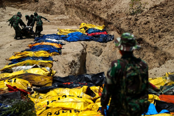 Soldiers move dead bodies of the victims of the earthquake and tsunami during a mass burial at the Poboya Cemetery in Palu, Central Sulawesi, Indonesia, October 2, 2018. (REUTERS)