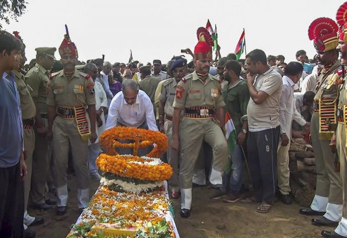 An official pays tribute to BSF head constable Narender Singh after his mortal remains arrived in his native village in Sonipat, Thursday, Sep 20, 2018. The body of Narender Singh, who had gone missing the near the international border in Ramgarh sector,