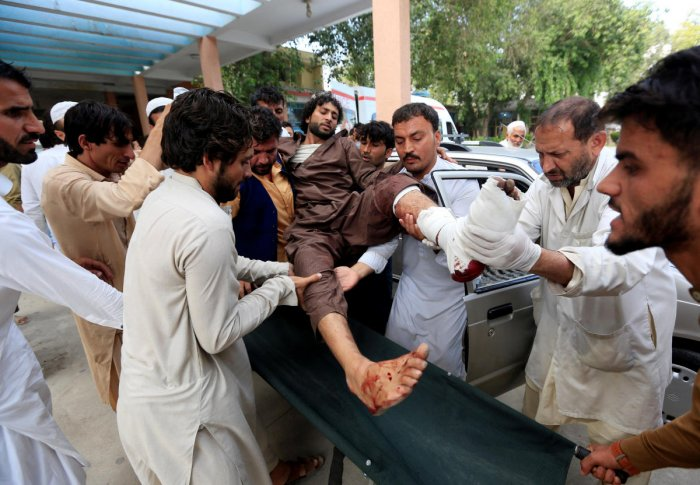 Afghan men carry an injured man to a hospital after a suicide attack in Jalalabad on October 2, 2018. Reuters