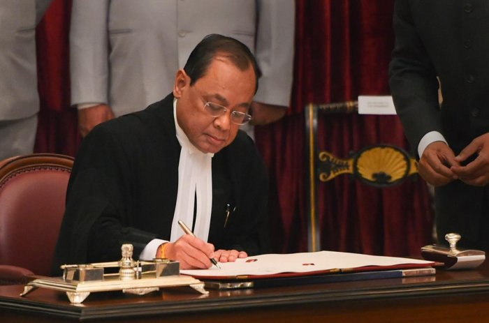 Justice Ranjan Gogoi signs the register after taking his oath of office on being appointed as the 46th Chief Justice of India, at Rashtrapati Bhawan in New Delhi, Wednesday, Oct 3, 2018. (PTI Photo)