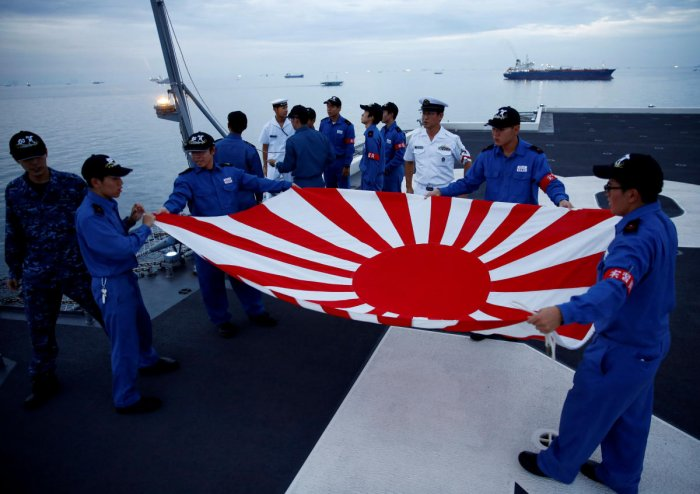 Sailors fold the Japanese naval ensign after a flag lowering ceremony on the deck of Japanese helicopter carrier Kaga anchored near Jakarta Port, Indonesia on September 21, 2018. Reuters