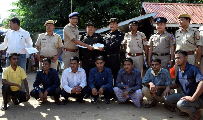 The seven Rohingya men to be deported sit as Indian and Myanmar security officials exchange documents before their deportation on India-Myanmar border at Moreh in the northeastern state of Manipur on Thursday. Reuters