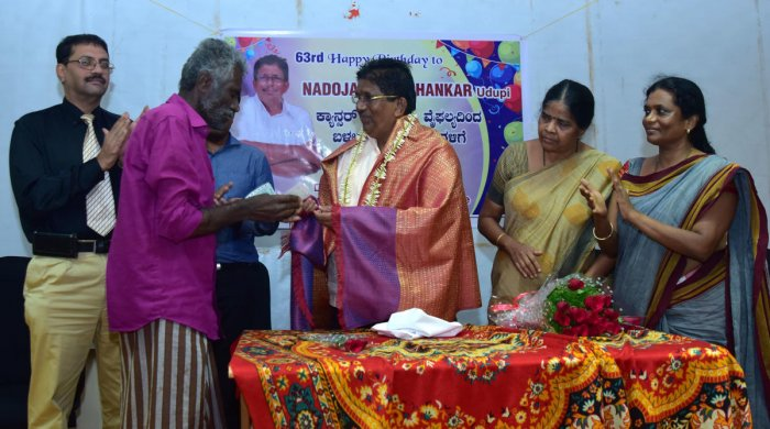 Nadoja awardee G Shankar presents a DD to a beneficiary at RAPCC Hall in the District Wenlock Hospital in Mangaluru on Thursday.