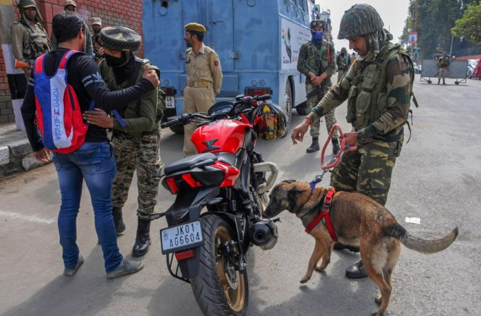 CRPF personnel check vehicles and motorcycles using sniffer dogs, ahead of polling for first phase of elections for urban local bodies in Kashmir, in Srinagar on Saturday. PTI