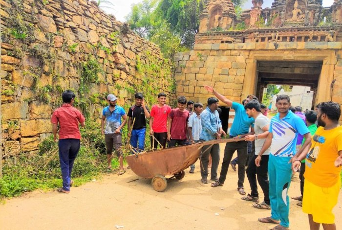Group members clearing the bushes around a fortress in Hagalwadi, Tumakuru; a village entrance.