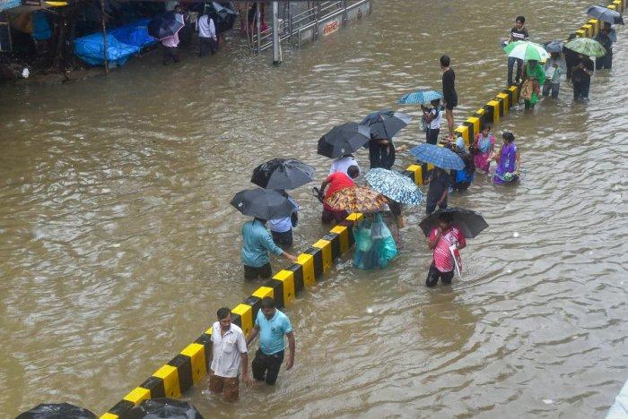 People wade through a waterlogged street following heavy rains, in Mumbai. PTI