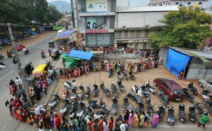 People queue up in front of the Mysuru Silk showroom, near Sri Chamarajendra Zoological Gardens, in Nazarbad, Mysuru, on Tuesday. (DH Photo by K S Gireesha)