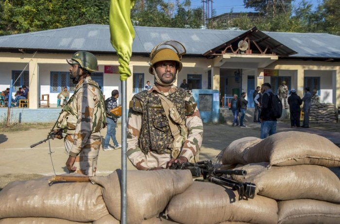 Security personnel stand guard at a polling station during the first phase of elections for urban local bodies, in Budgam district of central Kashmir, on Monday. PTI