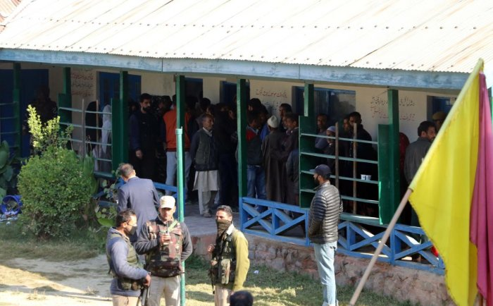 Voters wait in queues outside a polling station in Bemina area of Budgam district to cast their franchise during the first phase of urban local bodies election on Monday. DH photo / Umer Asif
