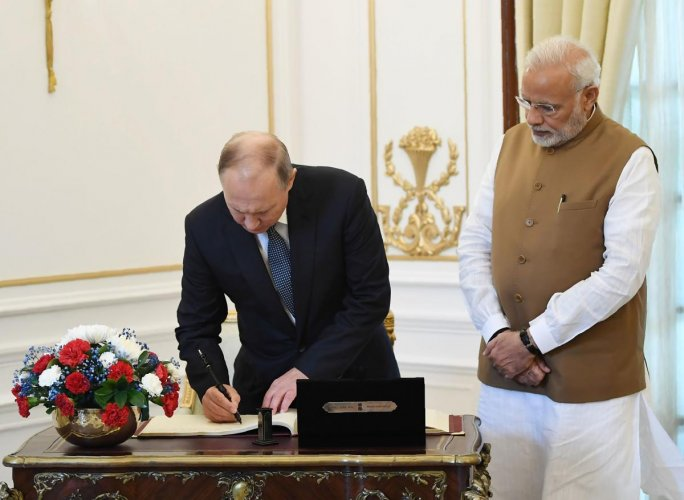 Russian President Vladimir Putin (L) signing the visitors book as Prime Minister Narendra Modi looks on at the Hyderabad House in New Delhi. (Photo by Handout/PIB/AFP)
