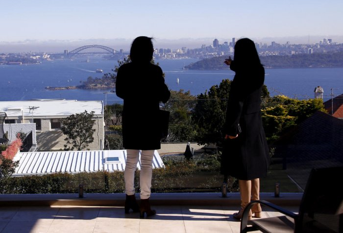 The Sydney Opera House and Harbour Bridge can be seen behind real estate agent and a potential buyer from Shanghai, during an inspection of a property for sale in the Sydney suburb of Vaucluse, Australia, July 11, 2015. Reuters File