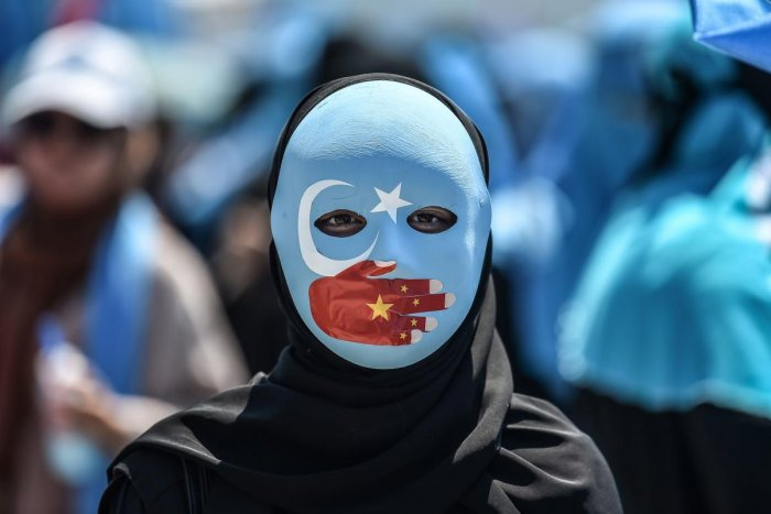 A demonstrator wearing a mask painted with the colours of the flag of East Turkestan and a hand bearing the colours of the Chinese flag attends a protest of supporters of the mostly Muslim Uighur minority and Turkish nationalists to denounce China's treat