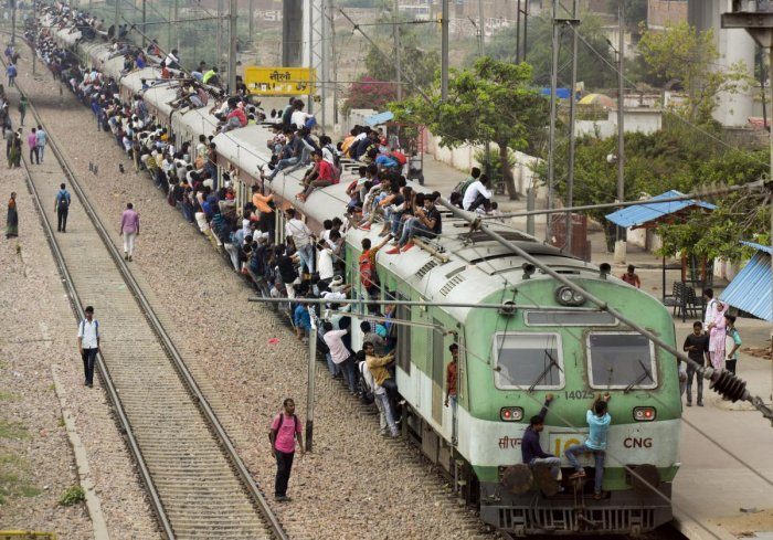 Commuters hang onto the doors and sit on the roof while travelling by a crowded train at Noli Railway Station near Ghaziabad. PTI