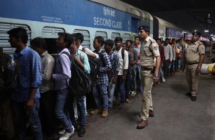 Railway police officers stand guard, as migrant workers from the northern state of Uttar Pradesh board a passenger train to depart from a railway station in Ahmedabad. PTI photo