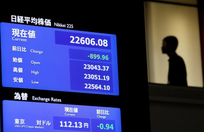 A man is seen behind an electronic board displaying the Nikkei average and Japanese yen rate againt the U.S. dollar at the Tokyo Stock Exchange in Tokyo, Japan, October 11, 2018. (REUTERS)