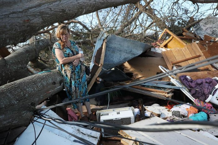 A woman stands among what is left of her home after Hurricane Michael destroyed it in Panama City, Florida, on October 11, 2018. She was inside her house when the tree fell crushing her house. AFP