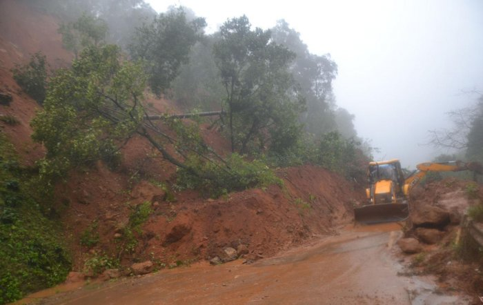 The earth mover pressed to service to clear the soil from NH 275 at Madenadu on Madikeri-Mangaluru road.