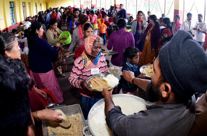 Food is served to flood victims at a relief centre at Suntikoppa in Kodagu district on Tuesday. DH Photo