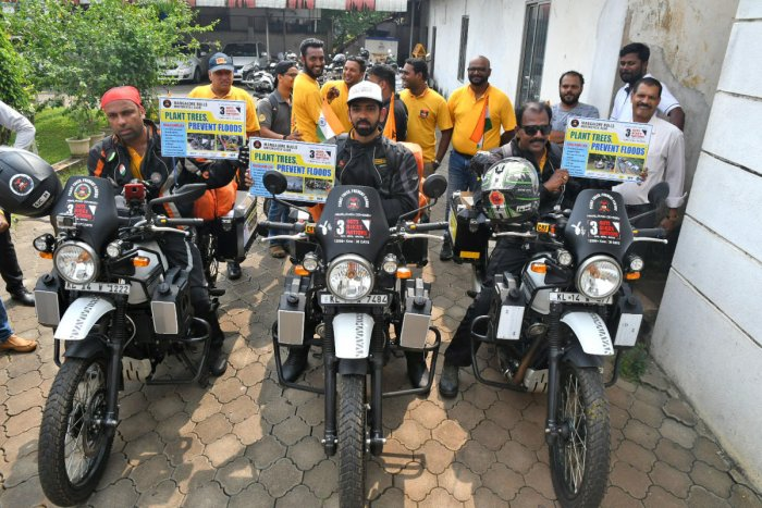 Three bikers hold placards highlighting the importance of afforestation prior to the start of their journey from the office of the Mangaluru Commissioner of Police on Thursday.
