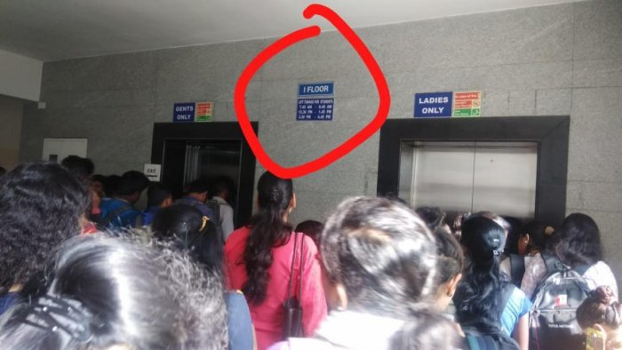 The board displaying the time schedule to use the lift in the background as students rush to take the lift. DH Photo