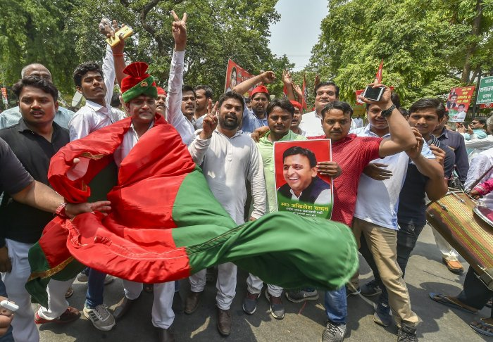 Samajwadi Party workers celebrate their party's success in Uttar Pradesh by-elections, outside their party office in Lucknow, on Thursday. PTI