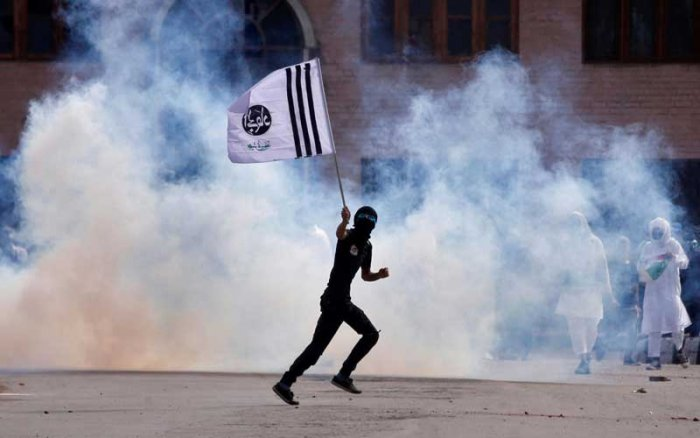 A protester holds a banner as he runs amid smoke from a tear gas shell fired by police during clashes that erupted after the Eid prayers, in Srinagar on Saturday. (Reuters)