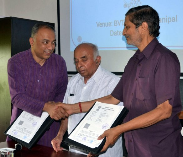 SELCO Foundation Chairman Harish Hande and Bharathiya Vikas Trust representative exchange an MoU on setting up a training centre at Manipal on Monday.