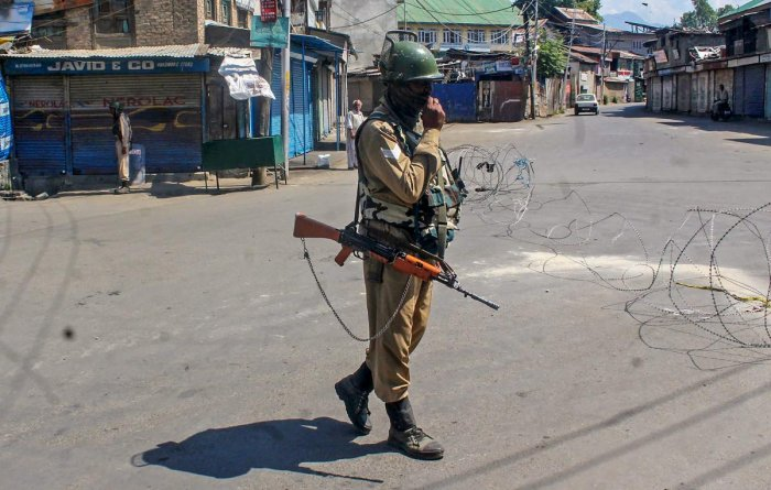 A CRPF personnel stands guard on a road during a strike called by the separatist leaders. PTI file photo