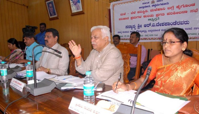 Revenue Minister R V Deshpande chairs a review meet on the rain relief works, at Zilla Panchayat auditorium in Chikkamagaluru on Wednesday. Deputy Commissioner M K Srirangaiah and Zilla Panchayat CEO Satyabhama look on. DH PHOTO