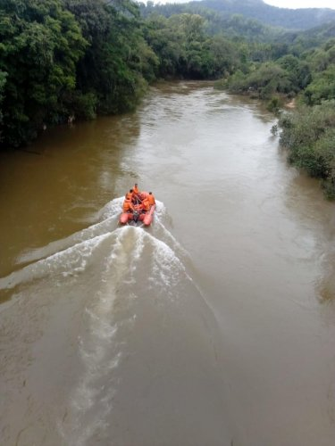 A NDRF search and rescue team sets out on the Tunga river to look for Umesh who was washed away in the river on Friday. DH photo.