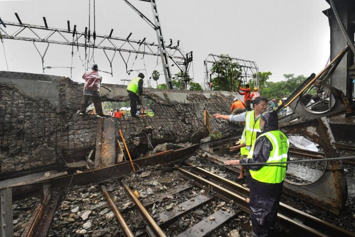 Rescue workers clear the debris of Gokhale foot overbridge that collapsed on the Western Railway tracks, at Andheri station following heavy rain, in Mumbai on Tuesday. PTI