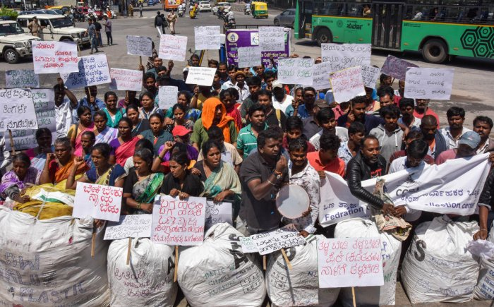 Workers of the dry waste collection centres stage a protest over pending wages outside Town Hall on Saturday. DH Photo
