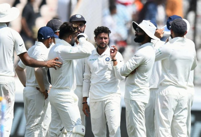 Kuldeep Yadav (C) celebrates with teammates the wicket of West Indies cricketer Kraigg Brathwaite during the first day's play of the second Test cricket match between India and West Indies at the Rajiv Gandhi International Cricket Stadium in Hyderabad on October 12, 2018. (AFP Photo)
