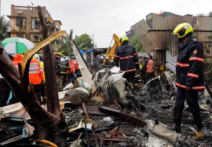 Firefighters inspect the site of a plane crash in Mumbai. Reuters